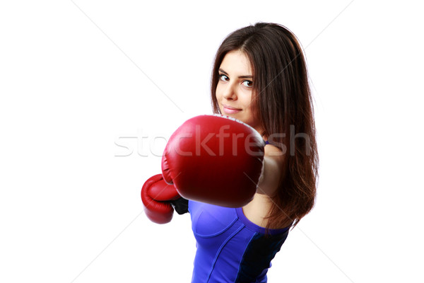 Young happy woman punching in camera with boxing glove isolated on white background Stock photo © deandrobot