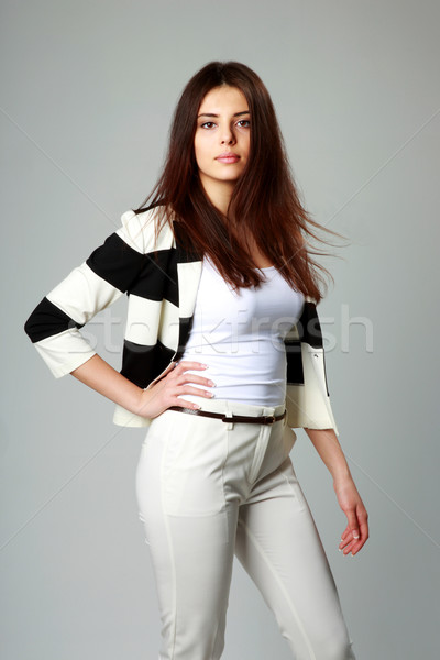 Young beautiful woman in casual clothes on gray background Stock photo © deandrobot