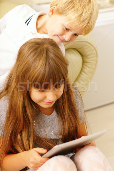 Brother and sister playing with tablet computer at home Stock photo © deandrobot