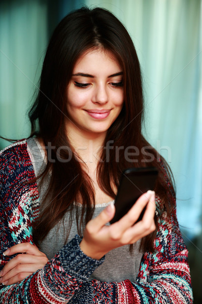 Smiling beautiful woman using smartphone at home Stock photo © deandrobot