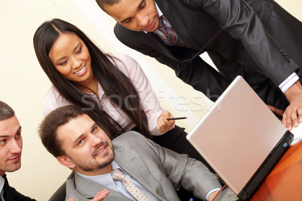 Mature businessman working on laptop with his multi ethnic business team Stock photo © deandrobot