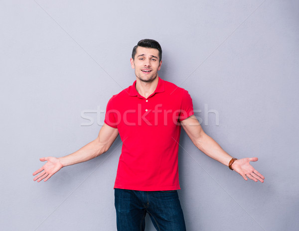 Handsome young man welcoming you with his arms open Stock photo © deandrobot