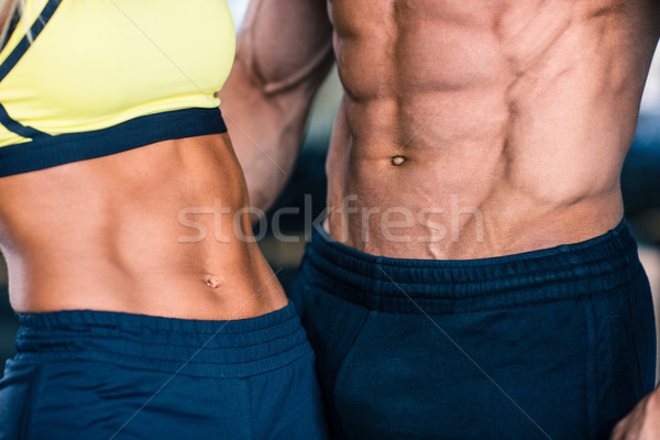 Muscular man's and sporty woman's torso Stock photo © deandrobot