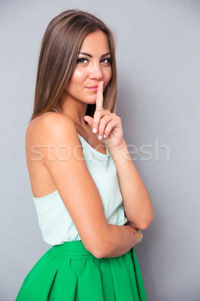 Csinos nő mutat ujj ajkak portré csinos Stock fotó © deandrobot
