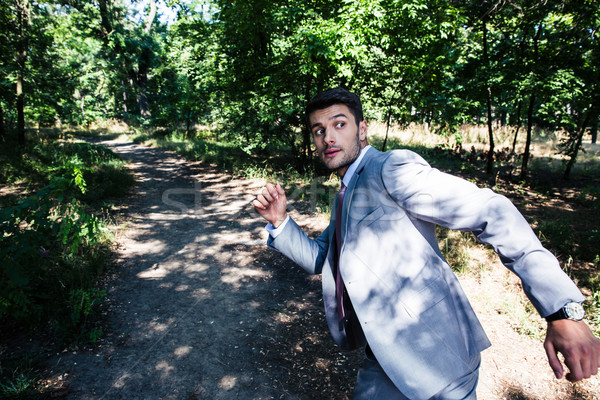 Businessman running away from something  Stock photo © deandrobot