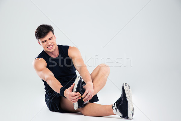 Athletic man suffering from pain in ankle  Stock photo © deandrobot