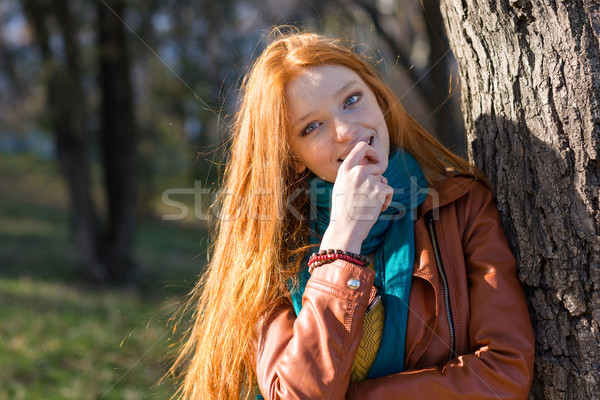 Pretty shy woman standing near the tree in park  Stock photo © deandrobot