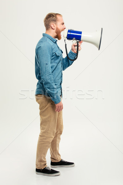 Side view portrait of a casual man screaming in megaphone Stock photo © deandrobot