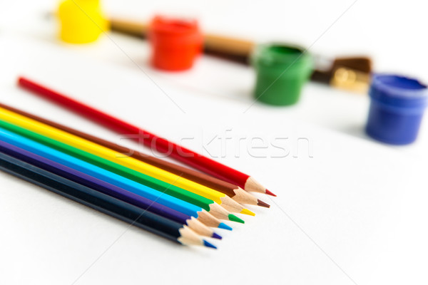 Stock photo: Colorful pencils for drawing lying near gouache paints and brushes