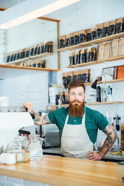 Bearded barista with tattooed hands in coffee shop Stock photo © deandrobot