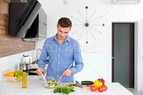 Handsome man in blue shirt mixing vegetables for salad  Stock photo © deandrobot