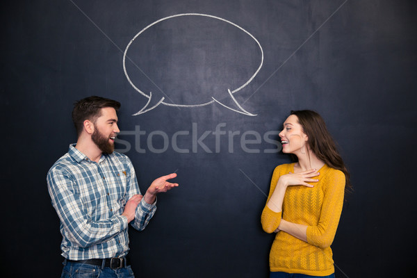 Happy couple talking over chalkboard background with drawn dialogue Stock photo © deandrobot