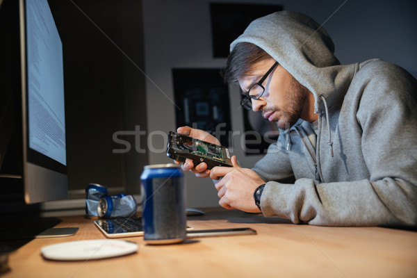 Serous man looking on broken hard disk at home Stock photo © deandrobot