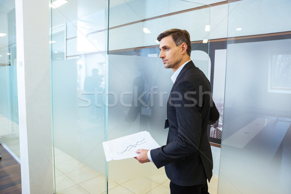 Confident businessman holding documents and entering the office Stock photo © deandrobot