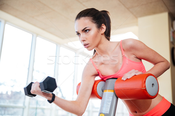 Focused sportswoman working out with dumbbels in gym Stock photo © deandrobot