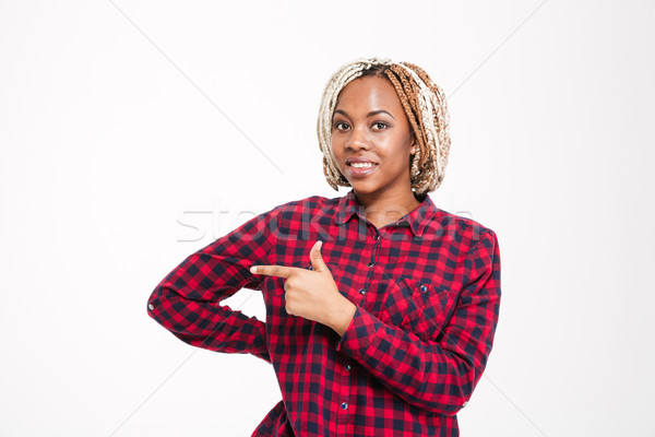 Smiling pretty young african american woman pointing away  Stock photo © deandrobot