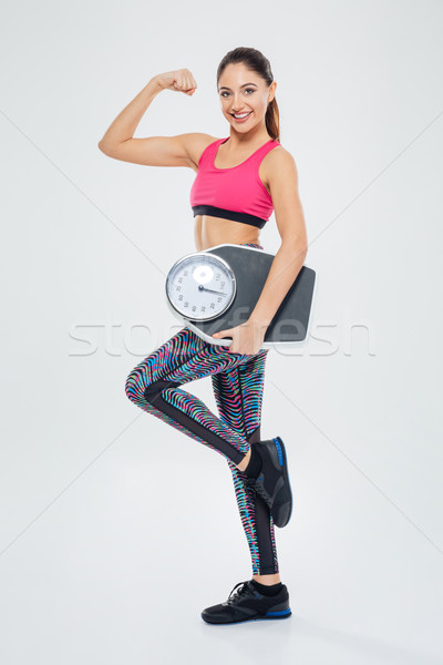 Happy success fitness woman holding weighing machine Stock photo © deandrobot