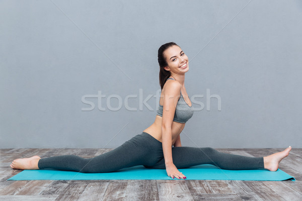 Young smiling girl in sportswear sitting on splits Stock photo © deandrobot