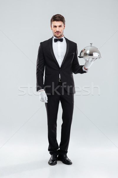Handsome young man waiter holding tray and lid Stock photo © deandrobot