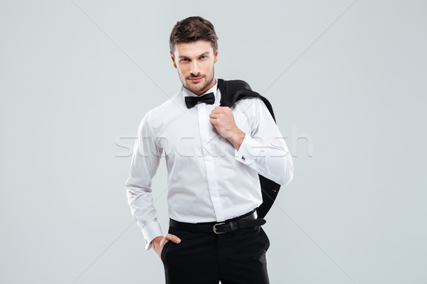 Gorgeous young man in tuxedo standing and holding his jacket Stock photo © deandrobot