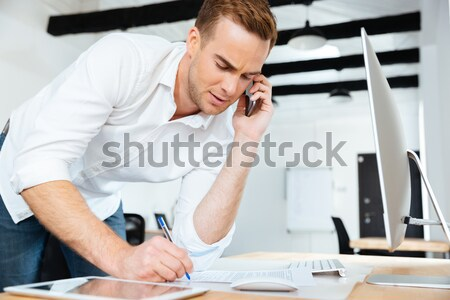 Stressed tensed young businessman suffering from headache Stock photo © deandrobot