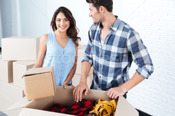 Young beautiful couple unpacking in new flat Stock photo © deandrobot