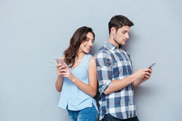Kız arkadaş izlerken erkek arkadaş telefon kıskanç Stok fotoğraf © deandrobot