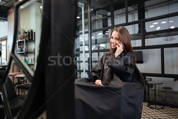 Woman talking on smartphone at hair salon Stock photo © deandrobot