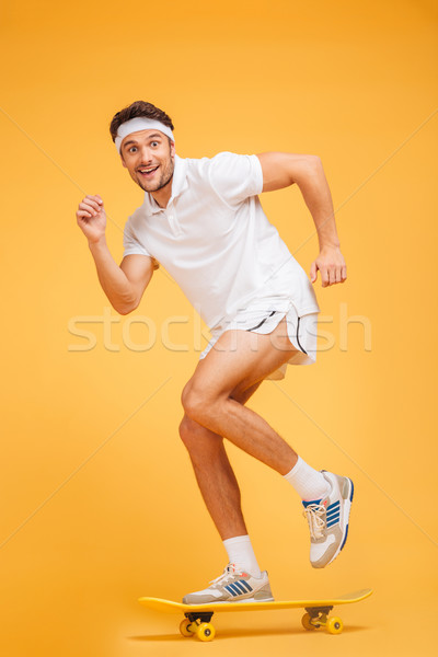 Stock photo: Full length portrait of a happy young sports man skateboarding