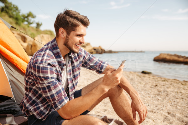 Smiling young man tourist using smartphone sitting in touristic tent Stock photo © deandrobot