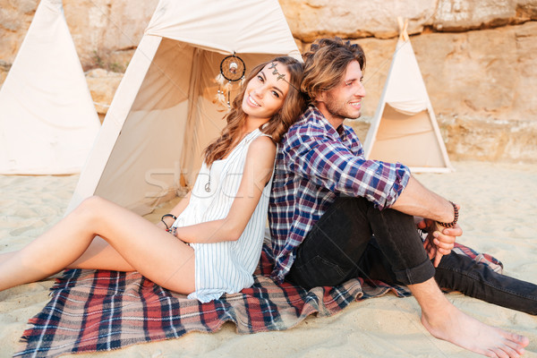 Stock photo: Couple sitting and resting near wigwam on the beach