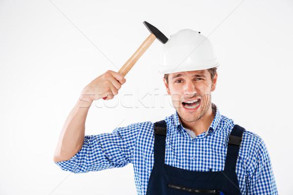 Builder applying hummer to his head in helmet Stock photo © deandrobot