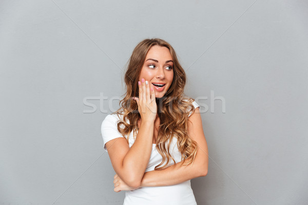 Portrait of happy surprised young woman with opened mouth Stock photo © deandrobot