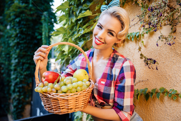 Happy charming pin-up girl with basket of fresh fruits Stock photo © deandrobot