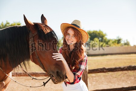 Cheerful young woman cowgirl standing with her horse in village Stock photo © deandrobot