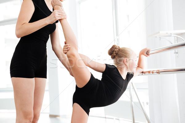 Little ballerina stretching with help of teacher in ballet class Stock photo © deandrobot