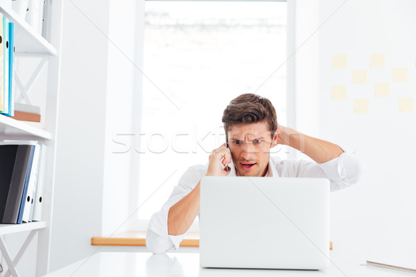 Disappointed young businessman talking on the phone and looking Stock photo © deandrobot