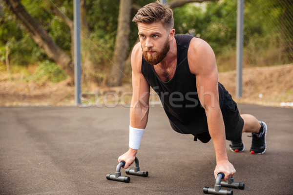 Muscular fitness man doing push-ups and using sports equipment Stock photo © deandrobot