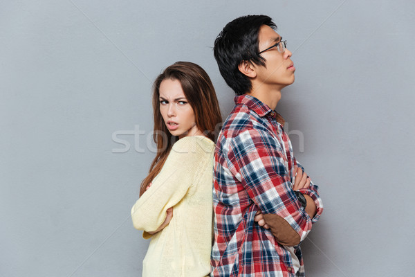 Unhappy young couple standing with arms crossed Stock photo © deandrobot