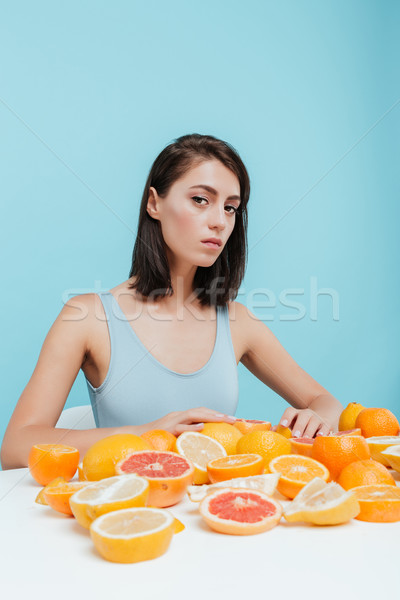 Closeup of woman at the table with oranges and grapefruits Stock photo © deandrobot