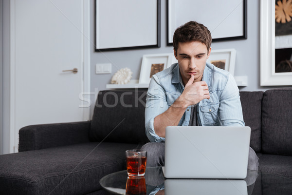 Man looking at laptop screen while sitting on sofa Stock photo © deandrobot