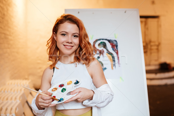 Young woman painter with red hair standing over blank canvas Stock photo © deandrobot