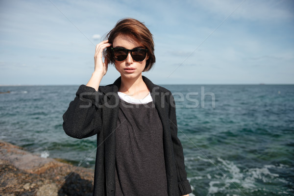 Attractive young woman in sunglasses standing on seashore Stock photo © deandrobot