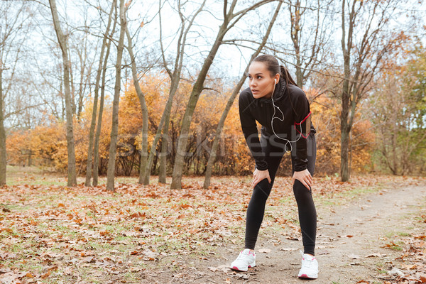 Young woman runner in warm clothes running in autumn park Stock photo © deandrobot