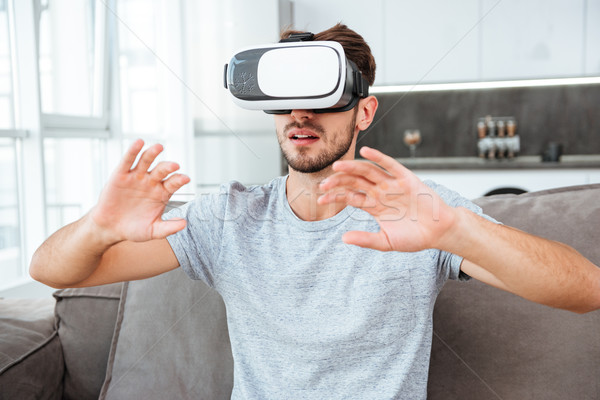 Young man wearing virtual reality device while sitting on sofa Stock photo © deandrobot