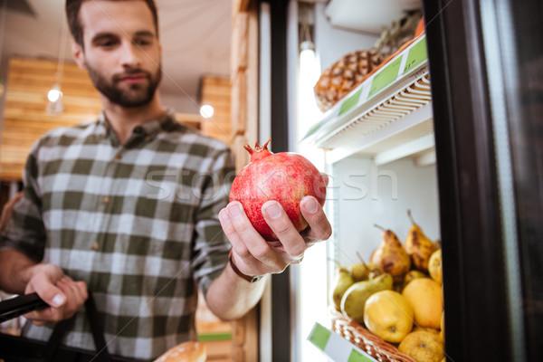 Homem escolher compra romã mercearia Foto stock © deandrobot