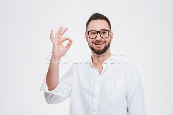 Mosolyog fiatal szakállas férfi pózol oké Stock fotó © deandrobot