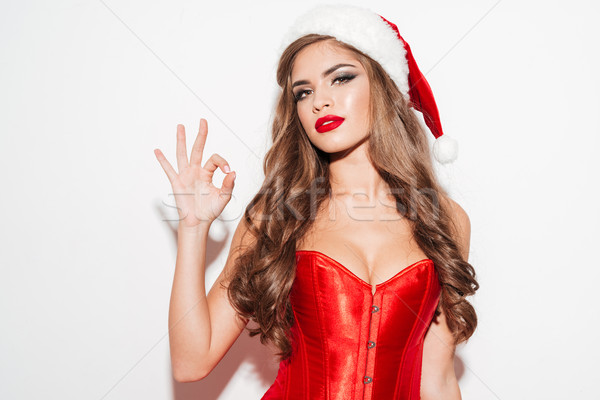 Seductive woman in red dress and hat showing okay gesture Stock photo © deandrobot
