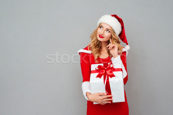 Wondered woman in red santa claus outfit holding christmas gift Stock photo © deandrobot