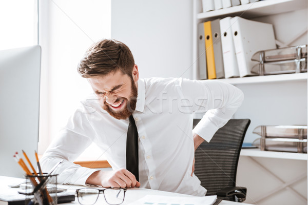Businessman with painful feelings holding his back. Stock photo © deandrobot